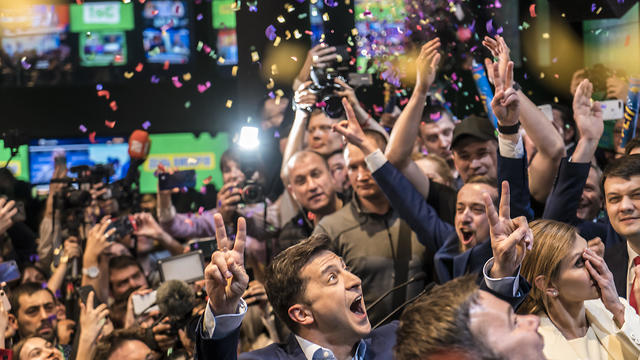 Volodymyr Zelenskiy (C) celebrates his apparent victory in Ukraine's presidential race at his election-day headquarters after polls closed on April 21