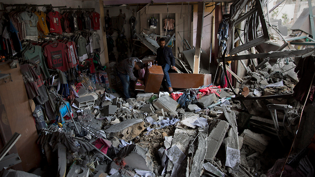 Gazans look at the damage to a shop hit by the IDF in Gaza City (Photo: AP)