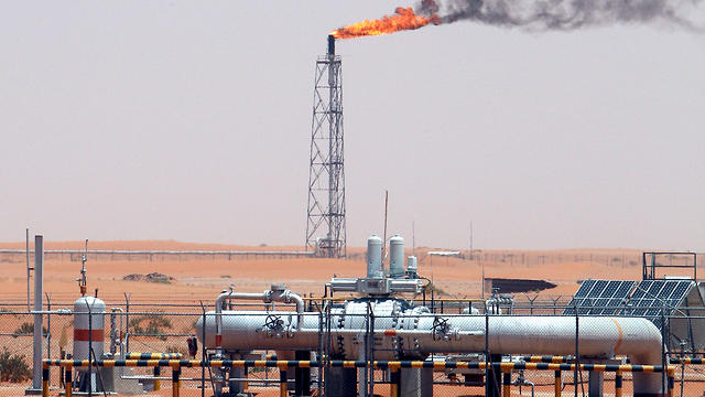 An image showing a gas flame behind pipelines in the desert at Khurais oil field, about 160 km from Riyadh, Kingdom of Saudi Arabia