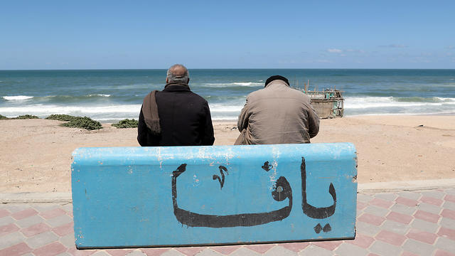 """Mahmoud Al-Assi, 73, who said that he was expelled with his family from Jafa, sits on a concrete bench adorned with a word reading """"Jaffa"""", on a beach in Gaza City"""