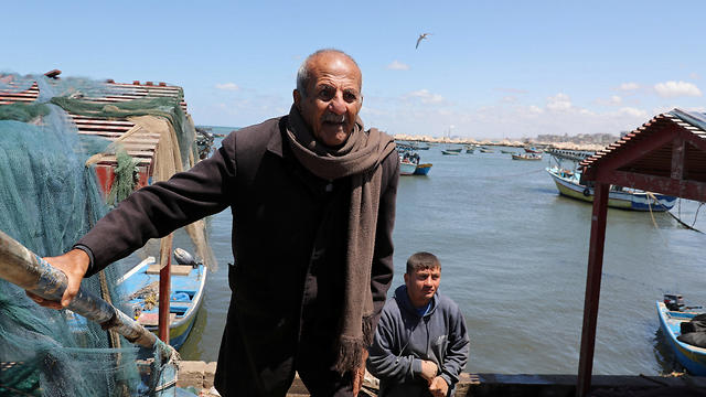 Palestinian fisherman Mahmoud Al-Assi, 73, who said that he was expelled with his family from Jafa when Israel was founded in 1948, walks at the seaport of Gaza City