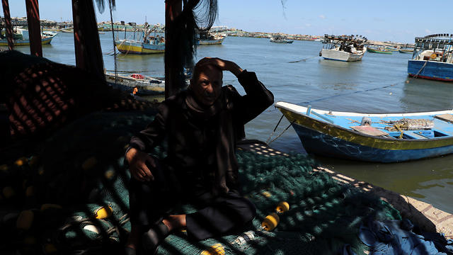 Palestinian fisherman Mahmoud Al-Assi, 73, who said that he was expelled with his family from Jafa when Israel was founded in 1948, sits at the seaport of Gaza City