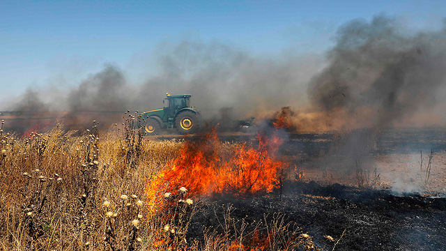 Fire started by incendiary balloons in Israeli community bordering Gaza  (Photo: AFP)