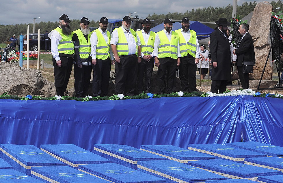ZAKA volunteers stand in front of mass grave