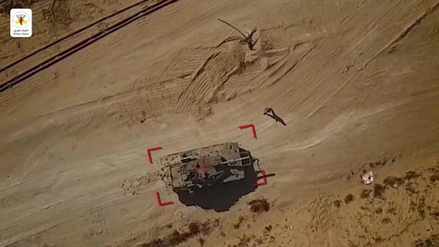 Israeli soldier walks up to a tank targeted by Islamic Jihad drone