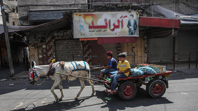Palestinians vendor ride a cart and pass by shops closed during a general strike in Gaza City due to Bahrain summit (Photo: EPA)