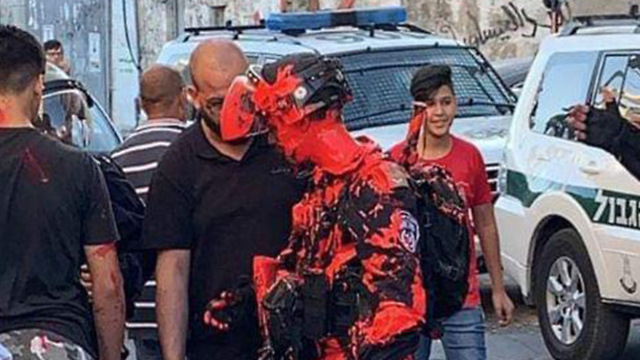 A police officer is covered in red paint during clashes in Issawiya