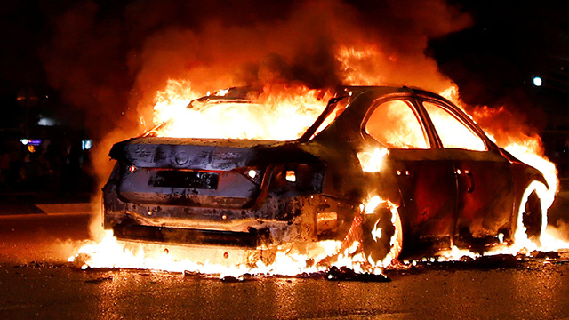 A car burns during protests outside Azrieli shopping mall in Tel Aviv (Photo: Reuters)