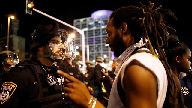 A protester confronts a police officer in Tel Aviv (Photo: Reuters)