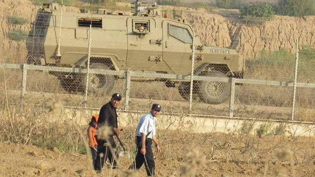 Hamas forces and IDF troops on either side of the Gaza border fence earlier this month