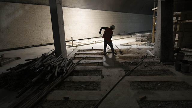 A worker cleans the floor at the construction site of a massive underground cemetery in Jerusalem, August 18, 2019