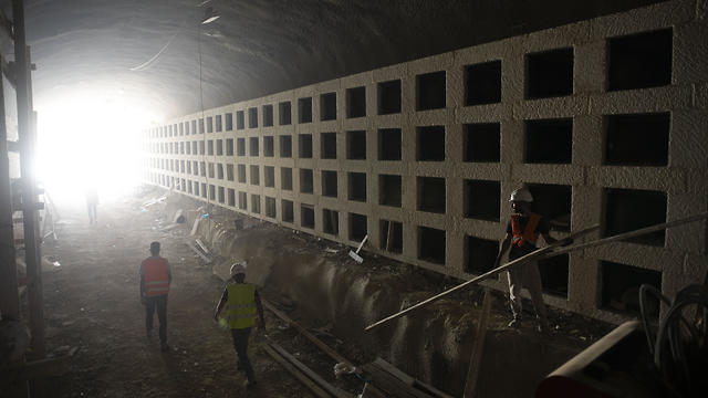 Workers walk at the construction site of a massive underground cemetery in Jerusalem, August 18, 2019