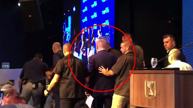 Netanyahu being rushed by his security guards off stage in Ashdod
