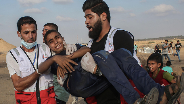 Palestinian medics evacuating a youth wounded during clashes with IDF troops on the Gaza border  (Photo: AFP)