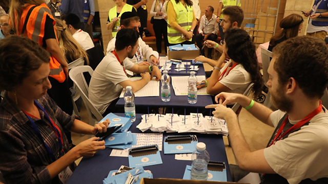 Central Elections Committee staffers count the double envelopes from Tuesday's ballot (Photo: Yitzhak Harari)