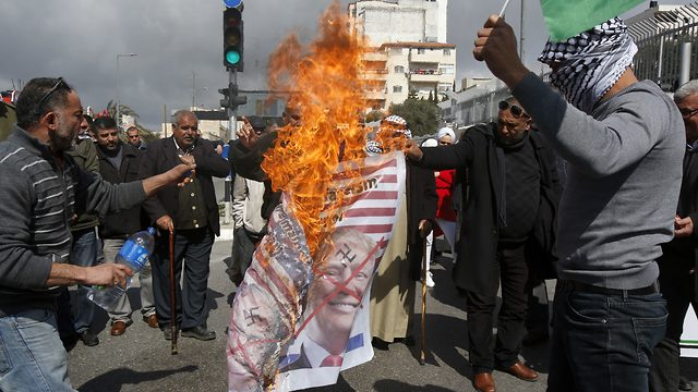 Palestinians in Bethlehem burn a banner depicting U.S. President Donald Trump and Prime Minister Benjamin Netanyahu to protest Israel's decision to withhold tax revenue owed to the PA, Feb. 19, 2019
