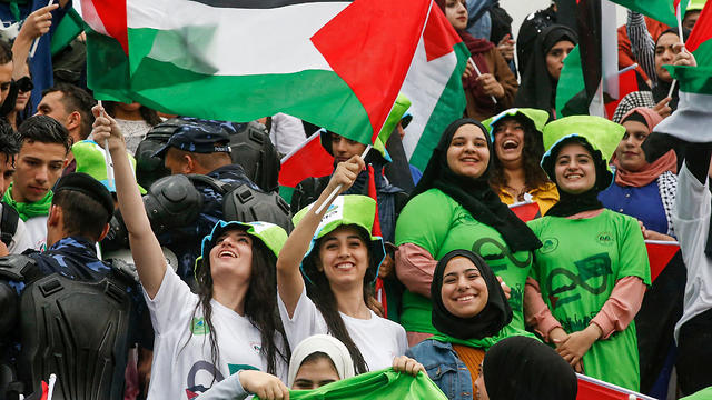 Women football fans wave Palestinian flags as they attend the World Cup 2022 qualifier match between Palestine and Saudi Arabia in the West Bank, Oct. 15, 2019