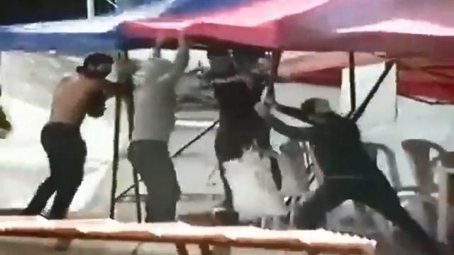 A still image taken from video showing Hezbollah members tearing down a protest tent in Beirut