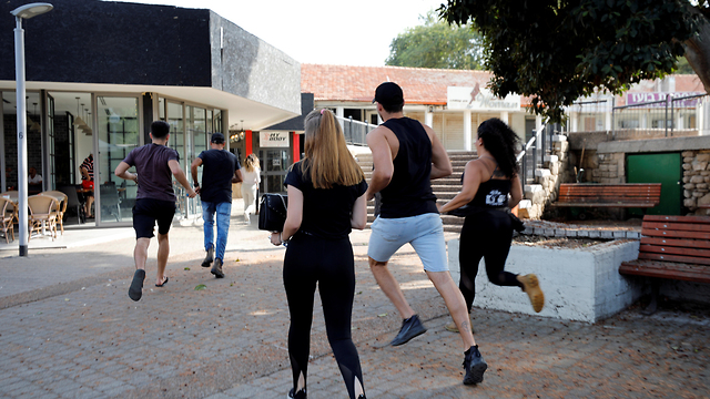 Residents of Ashkelon run for a bomb shelter during a rocket attack from Gaza (Photo: Reuters)