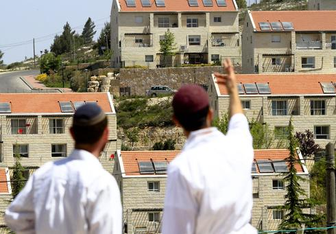 Two Jewish men standing in front of the West Bank settlement of Ofra