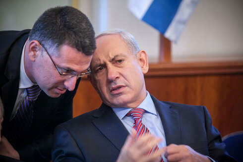 Gideon Saar, left, talks with Benjamin Netanyahu during his stint as a Likud cabinet minister in 2012