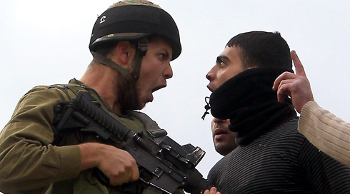 An IDF soldier confronts a Palestinian man in the West Bank