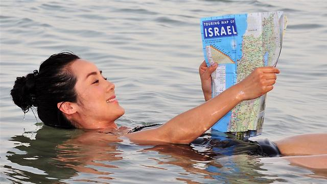 A tourist floating in the water at the Dead Sea