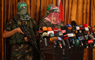 Members of Hamas' military wing holding a press conference in 2014