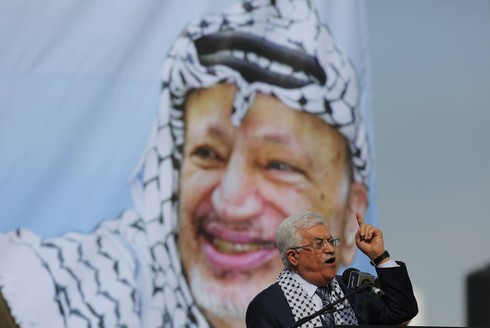 Palestinian President Mahmoud Abbas speaking with an image of his predecessor Yasser Arafat in the background