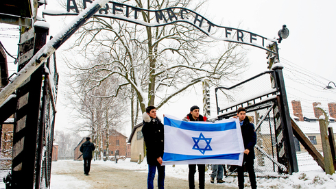 Youths holding the Israeli flag in front of the gate to the Auschwitz concentration camp