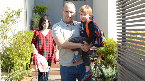 Naftali Bennet with his wife Gilat and his young son outside their home in Ra'anana