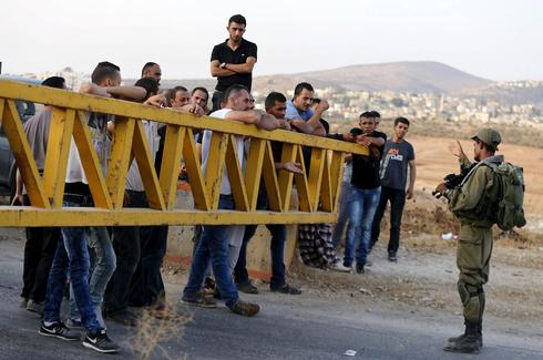 Palestinian workers waiting to cross an IDF crossing near the village of Beit Furik