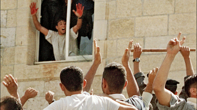 A Palestinian stands in the window of a Ramallah police station in October 2000, displaying the blood of two slain Israeli soldiers on his hands