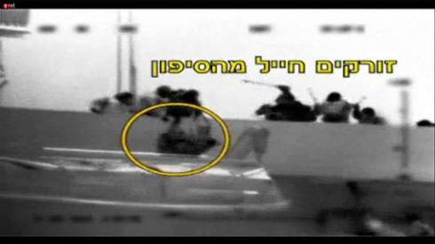 A still image from footage of the 2010 Gaza flotilla raid showing an IDF soldier being thrown overboard