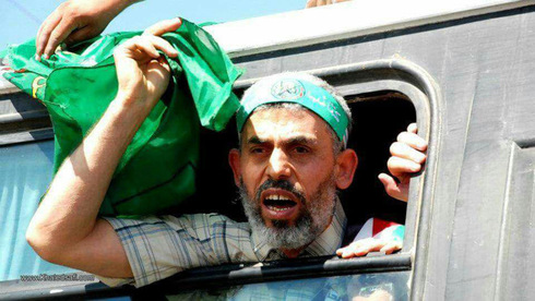 Yahya Sinwar waves a Hamas flag as he is released from an Israeli prison as part of the 2011 prisoner swap deal