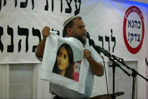 Benzi Gopstein during a memorial service for Meir Kahane, holding in protest a picture of Arab-Israel media personality Lucy Aharish