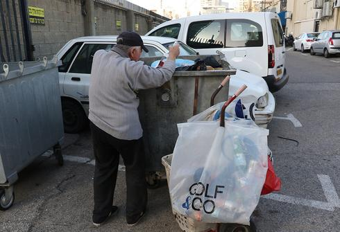 An elderly Israeli man searches in the trash for empty bottles that can be returned to stores for a small amount of money