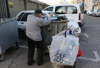 An elderly Israeli man searches in the trash