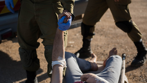 IDF troops assisting a wounded Syrian taken for treatment in the humanitarian hospital on the Golan Heights in 2017