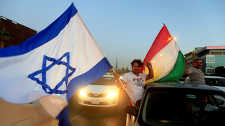 A Kurdish man holding the Israeli and Kurdish flags before the referendum on Kurdistan's independence
