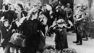 Boy holds his hands over his head while SS soldier points a submachine gun in his direction during the 1943 Warsaw Ghetto uprising