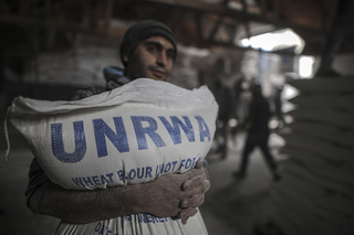 A Palestinian in Gaza receives a bag of flour from UNRWA depot