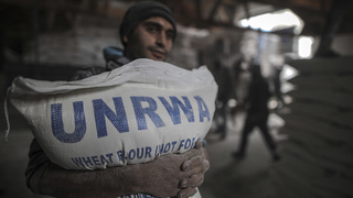 A Palestinian in Gaza receives a bag of flour from an UNRWA depot