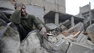 A Syrian man mourns over his destroyed home in Arbin in the eastern Ghouta region of Syria