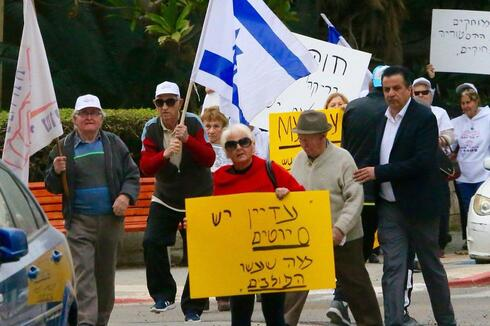 Holocaust survivors hold banners and wave an Israeli flag during a protest in front of Polish embassy in Tel Aviv on February 8, 2018, against a controversial bill that made it a crime to hold Poland responsible for Nazi crimes