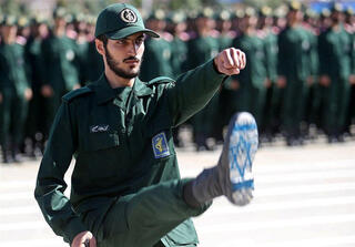 An Iranian soldier shows off the Israeli flag drawn on the sole of his shoe