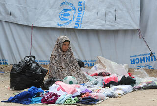A Syrian girl sells second-hand items in the Al-Hol camp for displaced people in northeastern Syria
