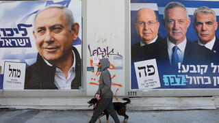An Isrseli man walks past campaign posters for Benjamin Netanyahu and Benny Gantz ahead of the March 2020  elections