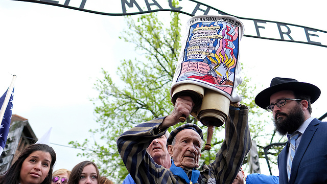 A Holocaust survivor holds up a Torah scroll at the gates of Auschwitz death camp during a previous March of the Living