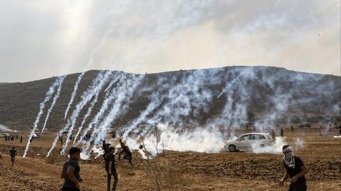 Tear gas fired by IDF troops falls among Palestinians protesting the construction of an outpost near the West Bank settlement of Shiloh, Oct. 17, 2019